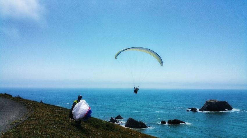 Paragliding off the cliffs! Two People Chartreuse  White Background Zen Copy Space Blue Moment Timeless Freedom Sport Extreme Sports Thrill Paragliding Parachute Extreme Sports Sea Sport Beach Water Blue Sky Horizon Over Water Calm Countryside Tranquil Scene Coast Idyllic Ocean Tranquility