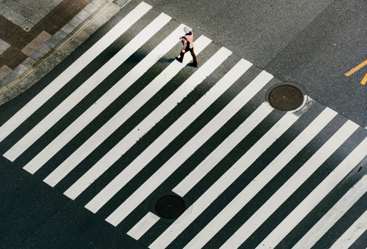 High angle view of woman walking on zebra crossing