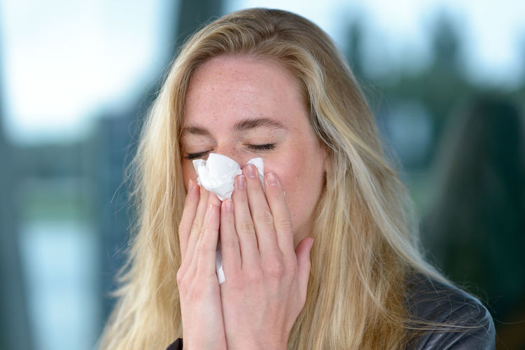 Close-up of woman sneezing