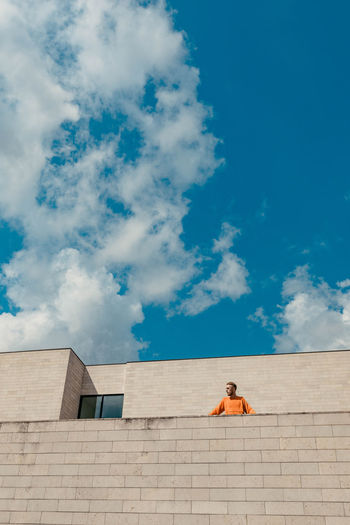 Low angle view of man standing at building terrace