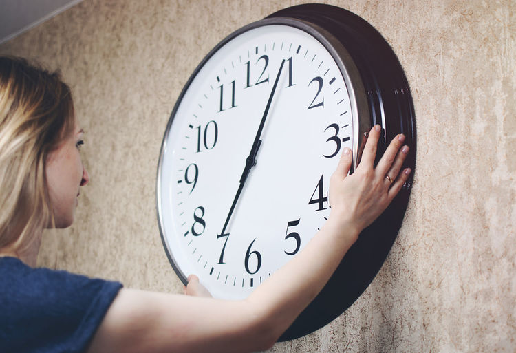 Side view of mid adult woman touching clock on wall