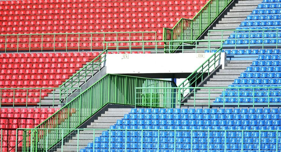 Blue and red bleachers in empty stadium
