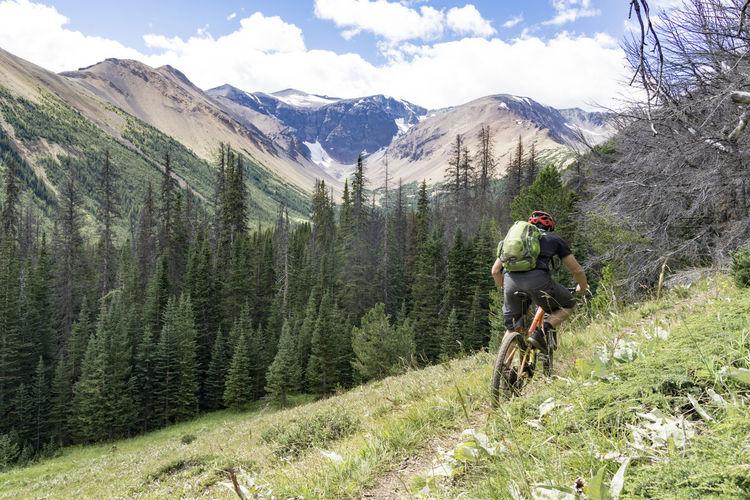 Rear View Of Man Riding Bike On Mountain