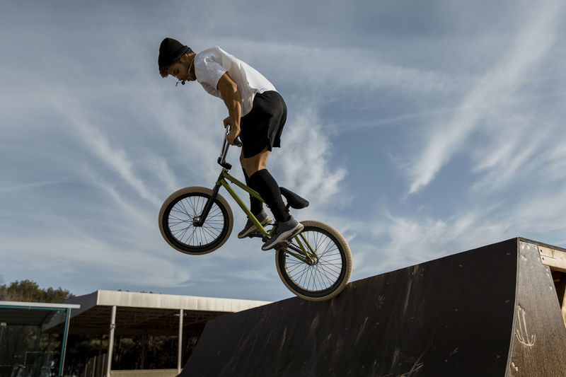 Low angle view of man riding bicycle against sky