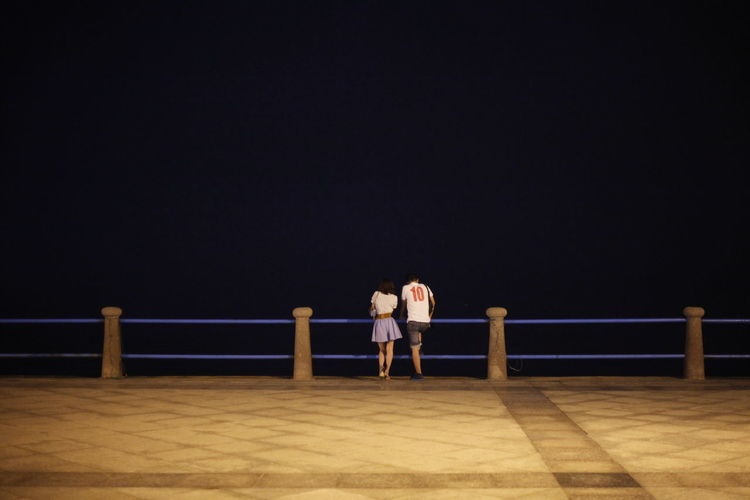 Rear view of couple standing by railing on promenade at night