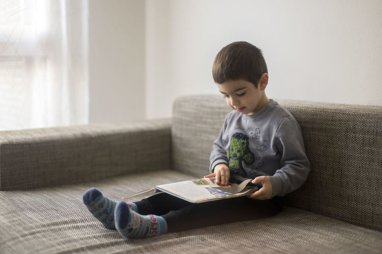 Full length of boy reading sitting on sofa