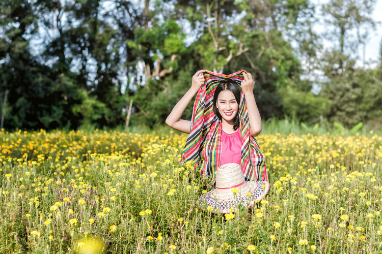 Portrait of young woman standing amidst marigold flowers on field