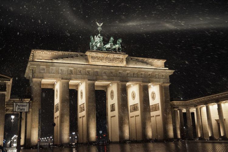 Brandenburg gate against sky during winter at night