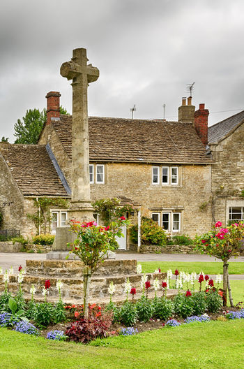 Stone cross in flower bed on grassy lawn in Castle Combe Village in Wiltshire, England. Architecture Castle Combe Cloud - Sky Cotswolds Cottage Day Destination Flower Flower Bed No People Outdoors Overcast Quaint  Quaint Village Scenic Sky Stone Stone Cross Village Wiltshire