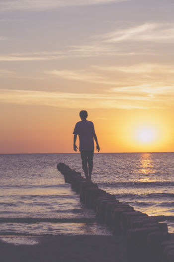 Man looking at sea against sky during sunset