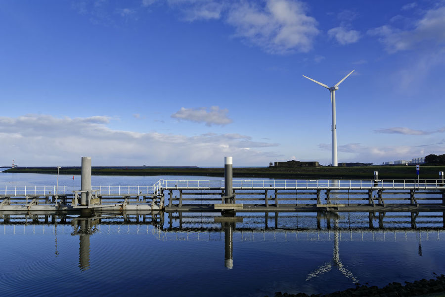 Reflections In The Blue Alternative Energy Beauty In Nature Blue Cloud - Sky Day Fuel And Power Generation Industrial Windmill Nature No People Outdoors Scenics Sea Sky Tranquility Water Wind Power Wind Turbine Windmill