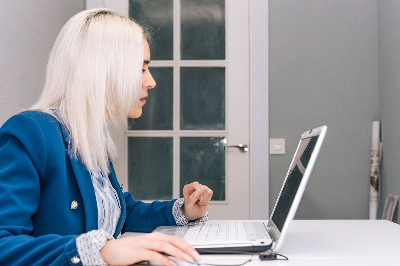 Young blonde woman with platinum hair dressed in a blue blazer teleworking from home with the laptop