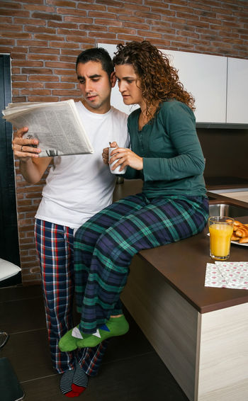 Couple having breakfast in the kitchen and reading the newspaper Vertical Socks Modern Brick Wall Croissant Surprised Serious Portrait Biscuits Sharing  Morning Together Orange Juice  Coffee Indoor Real Two Young Woman Curly Hair Wife Standing People Married Man Male Lifestyle Husband Talking Caucasian Home Girl Female Entertainment Watching Interested Kitchen Worried Looking Newspaper Bad News Reading Breakfast Pajama Couple Concerned