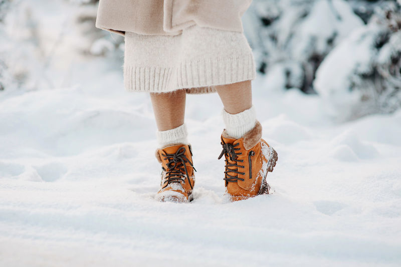 Warm winter boots in the snow. a girl in a beige faux fur coat walks through a snowy forest. fashion
