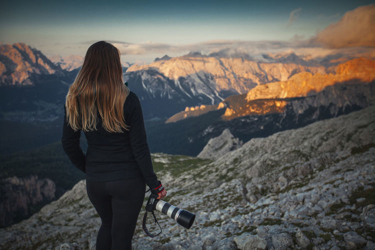 Rear view of woman photographing while standing against mountains during sunset