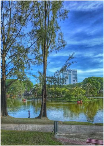 Wondering Kids Tree Sky Water Lake Cloud - Sky Built Structure Outdoors Architecture Day Blue Nature Grass Real People Growth Building Exterior Beauty In Nature Men City One Person People
