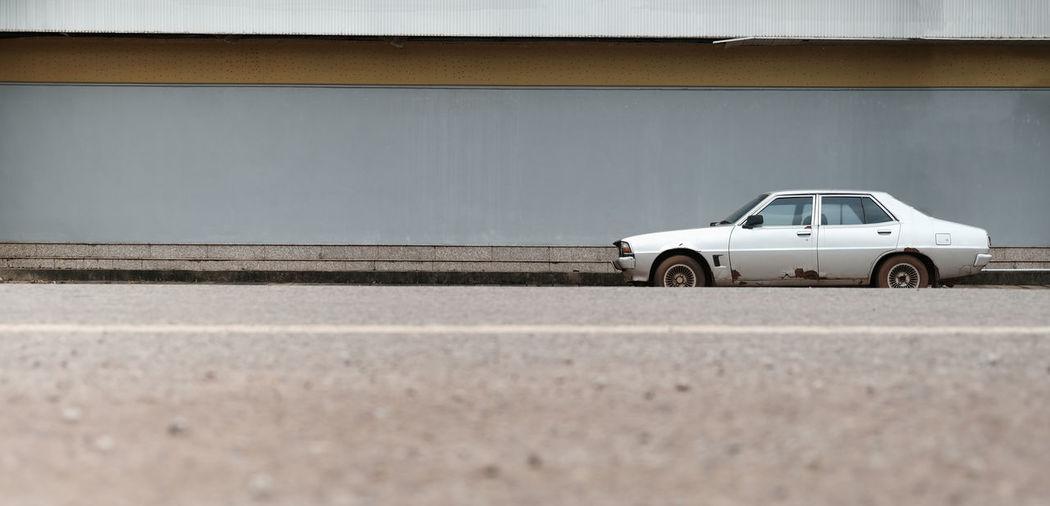 Car on street against wall