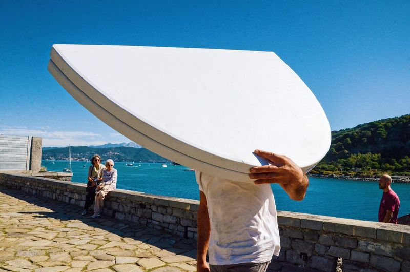 Man standing by sea against clear blue sky