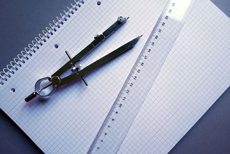 High Angle View Of Drawing Compass And Ruler On Spiral Book
