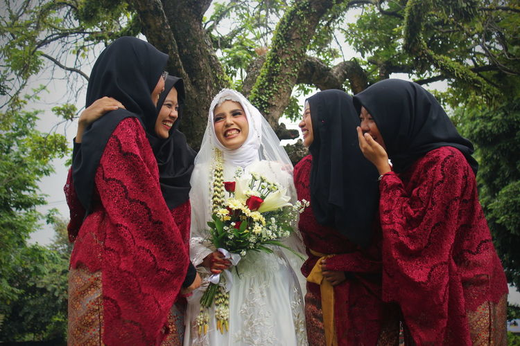 Cheerful bride and bridesmaids standing against tree