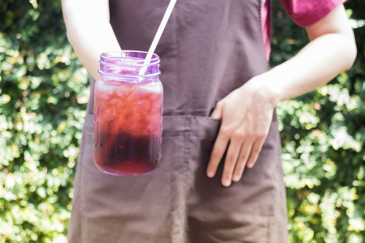 Midsection of woman holding drink in jar outdoors
