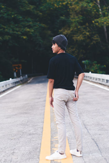 Rear view of young man standing on footpath