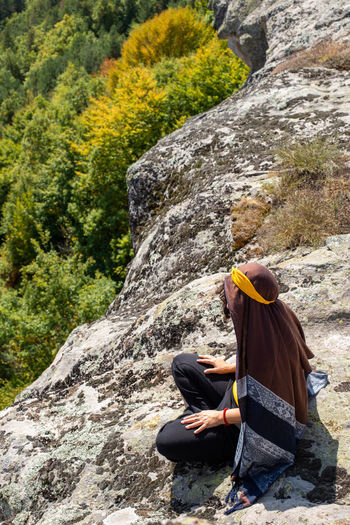 High angle view of woman sitting on rock outdoors