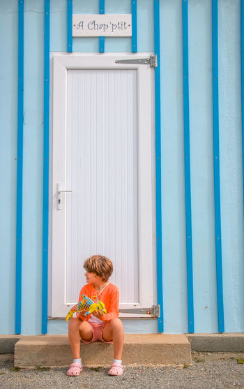 Day Loire Atlantique Sea Seaside Child Childhood One Person Full Length Sitting Architecture Lifestyles Built Structure Real People Casual Clothing Leisure Activity Text Front View Blue Shorts Girl Sitting Colors Lines Step Waiting Looking Blue And Orange Contrast Stuffed Animal