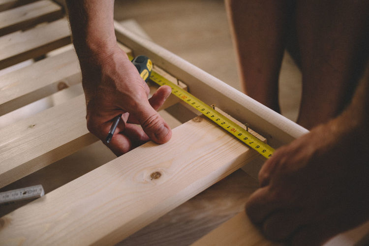 Midsection of man measuring wood at home