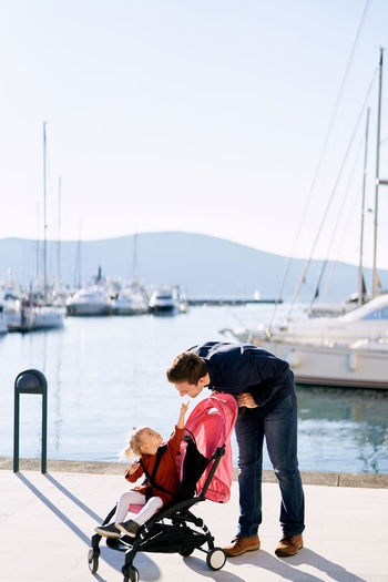 Father and daughter standing at harbor