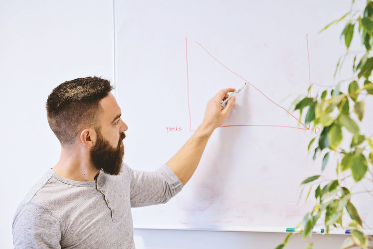 One Person Real People Wall - Building Feature Young Adult Indoors  Men Art And Craft Whiteboard Holding Casual Clothing Young Men Board Headshot Lifestyles Adult Mid Adult Waist Up Beard Home Improvement Studing Business Idea Office Working Graphic Modern Caucasian Ethnicity Beadred Man Handsome Hipster