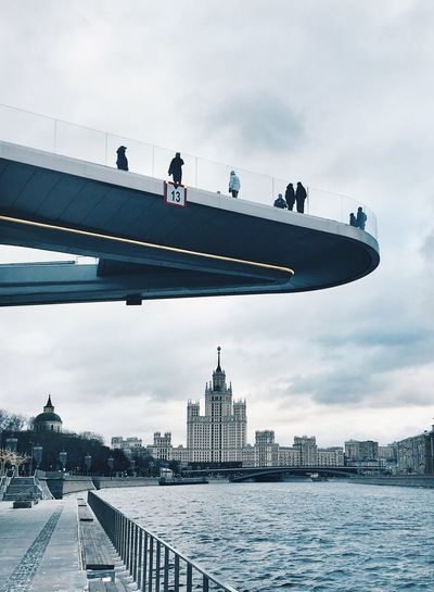 People standing over river on bridge in city