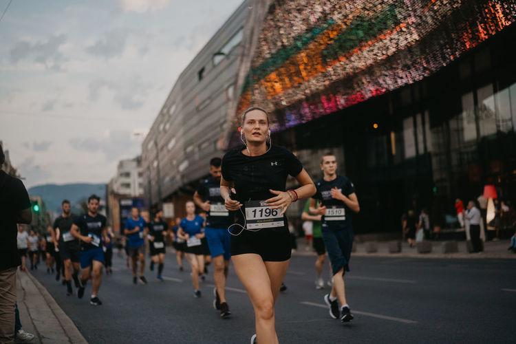 People running on street in city