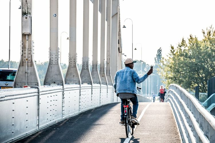 Faded. Bycicle Deventer, The Netherlands Netherlands Faded Morning Europe EyeEm Best Shots Light City Headwear Politics And Government Men Bicycle Cycling Helmet Road Cycling Rear View Bridge - Man Made Structure Bicycle Rack Racing Bicycle Bicycle Lane Biker