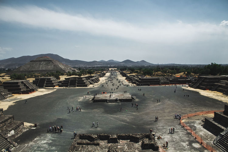 Aerial view of tourists at ancient pyramids against sky
