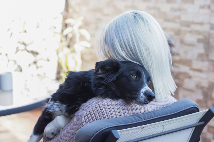 Rear view of woman sitting with dog