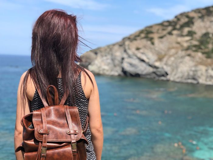 Water Sea Real People Lifestyles One Person Leisure Activity Women Nature Beauty In Nature Adult Rear View Focus On Foreground Day Hairstyle Sky Rock Long Hair Rock - Object Outdoors