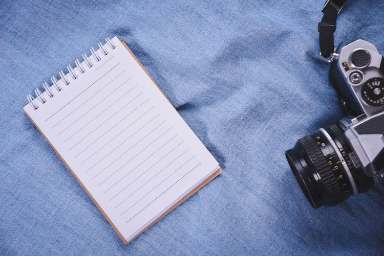 Close-up of camera and spiral notebook on table