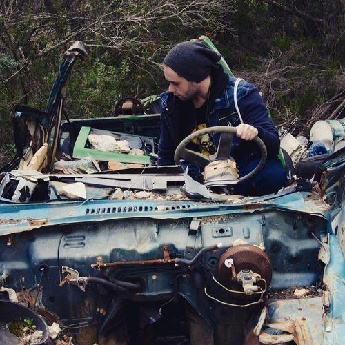 Man sitting in abandoned damaged car at garbage dump