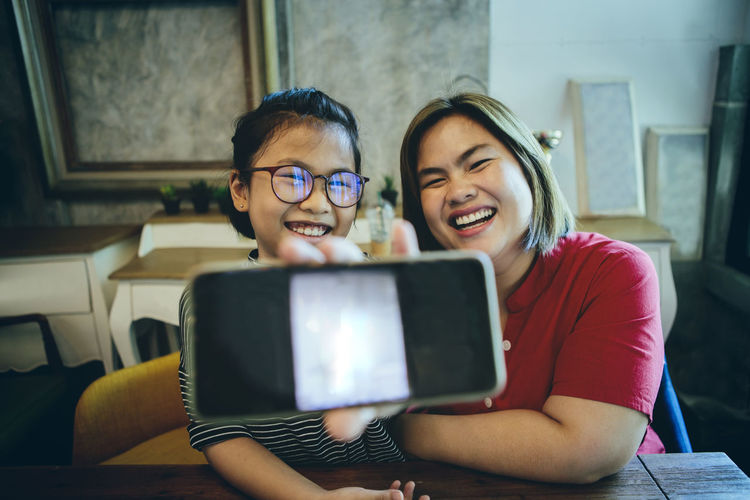 Asian mother and daughter showing smart phone screen and laughing with happiness face