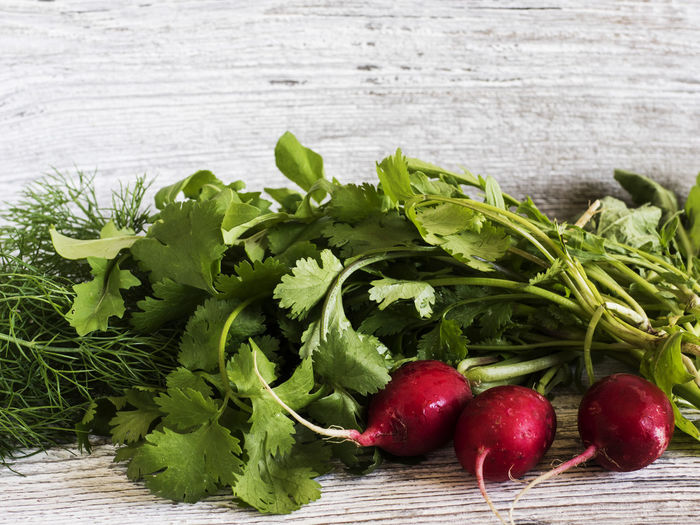 High angle view of radishes and herbs on wooden table