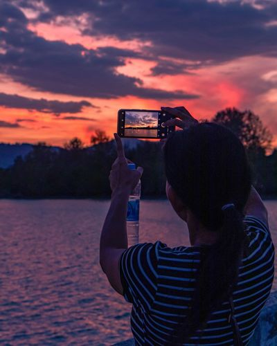 Man photographing with mobile phone against sky during sunset