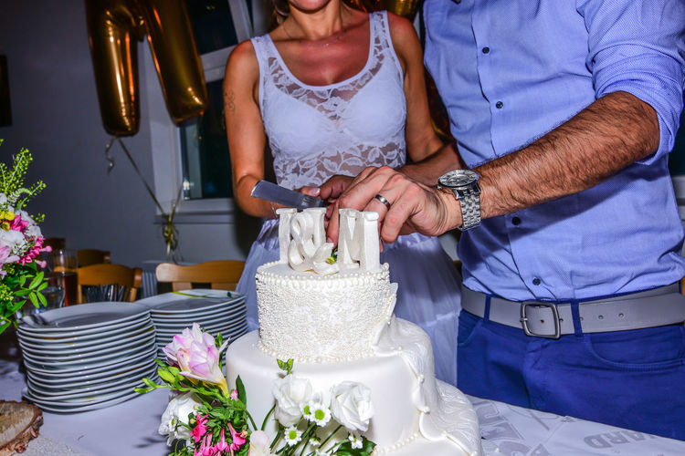 Midsection of couple cutting wedding cake on table