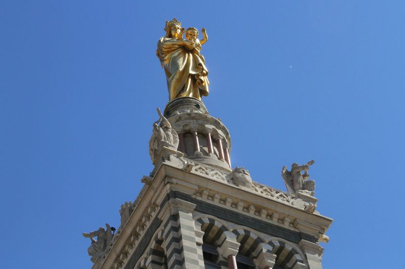 Low angle view of virgin mary and jesus christ sculptures on top of notre dame de la garde