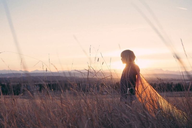 Rear view of woman on field against sky during sunset