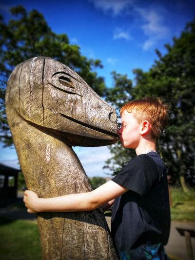 Side view of boy against sky