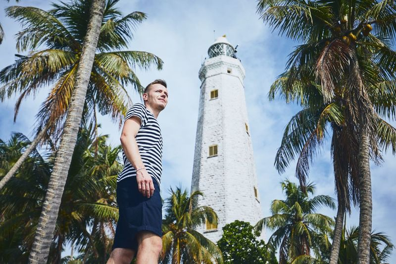 Young man looking away under palm trees against lighthouse. Coastline in Sri Lanka. Palm Tree Men Travel Destinations Travel Sri Lanka Vacations Leisure Activity Casual Clothing One Person Real People Lifestyles Nature Tropical Climate Outdoors Coast Exploring Freedom Lighthouse Architecture Landmark Young Adult Building Exterior Wanderlust Tourism Direction
