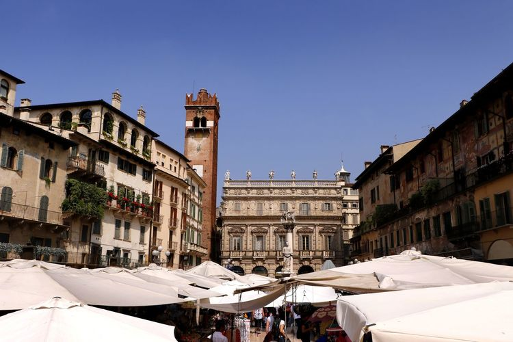 Above the market stalls in the Piazza delle Erbe in Verona, Italy Historical Building Market Travel Photography Architecture Blue Building Building Exterior Built Structure City City Life Clear Sky High Viewpoint History Market Stall Marketplace Outdoors Piazza Piazza Delle Erbe Stalls The Past Tourist Destination Town Travel Destination Urban Vacation Destination