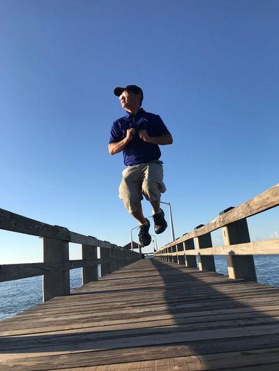 Man jumping on footbridge against clear sky
