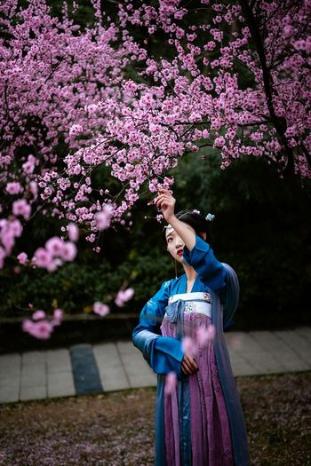 Woman with pink flowers against tree